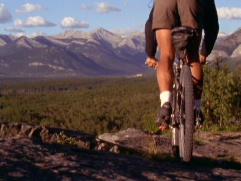 vidéos et rushes de rider on mountain bike descending trail - un seul homme d'âge moyen