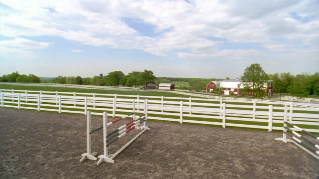 rider show jumping horse over fences in ring with view of stable in background - pferdestall stock-videos und b-roll-filmmaterial