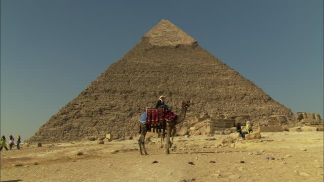 a rider sits atop a camel near the pyramid of khafre. - cultura egiziana video stock e b–roll
