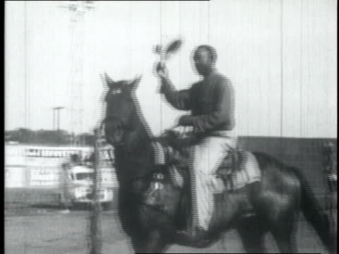 1950 ws rider sits on his horse and waves his hat / united states - カウボーイ点の映像素材/bロール