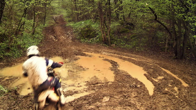 hd crane: mx rider splashing through muddy trail - mud stock videos & royalty-free footage