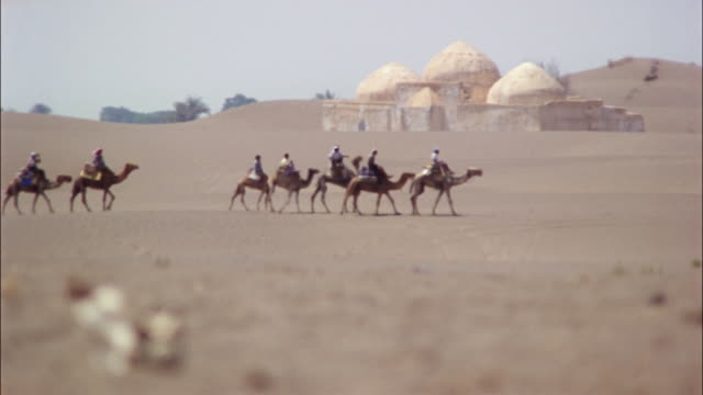 riders on camels walk by a mosque in yemen. - イエメン点の映像素材/bロール