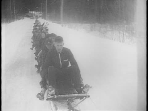 riders perched on long bobsled / bobsled tears through sign touting winter carnival / montage of bobsled traveling through snow, clipping cameraman,... - danger stock videos & royalty-free footage