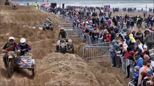 riders race down the beach during the adult quad and sidecar race during the 2016 hydrogarden weston beach race in westonsupermare southwest england... - sidecar stock videos & royalty-free footage