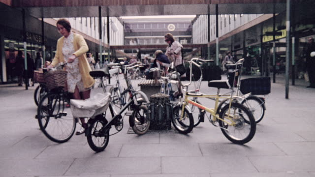 1974 montage riders removing bicycles from racks in a parking area and an outdoor market square / united kingdom - 1974 stock videos & royalty-free footage