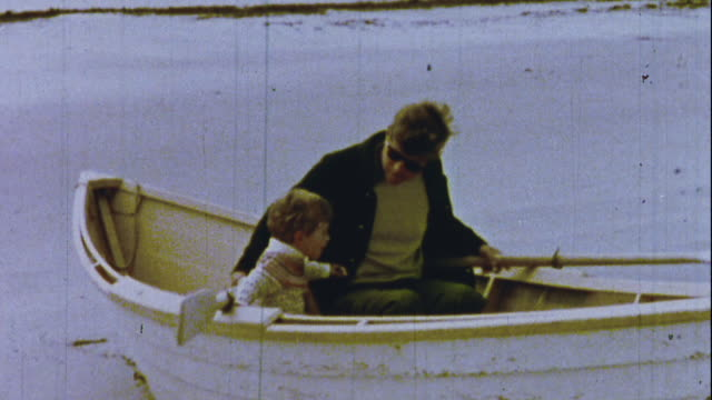 jfk rides in the back of a boat and plays with jfk jr - john f. kennedy politik stock-videos und b-roll-filmmaterial