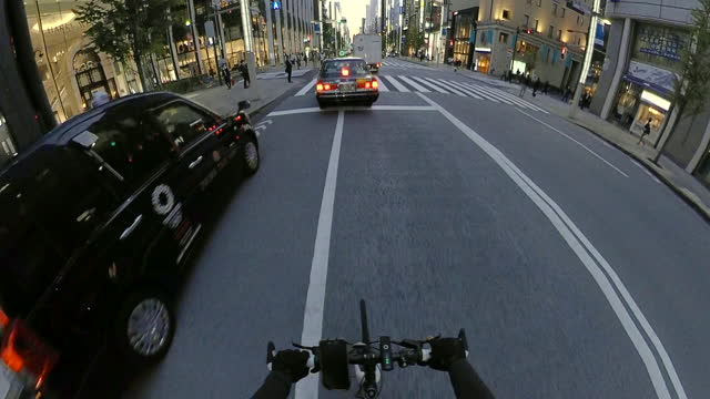 pov riding a bicycle in the city. riding bikes through ginza at dusk. tokyo japan. concept of delivery services. action camera shoot. - plusphoto stock videos & royalty-free footage
