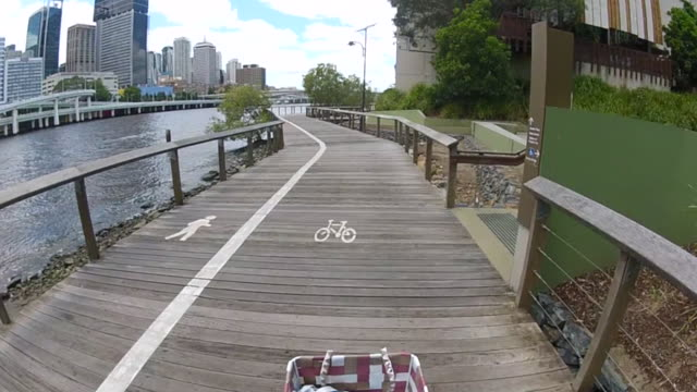 Riding a bicycle through the city, in a river path, Brisbane (POV)