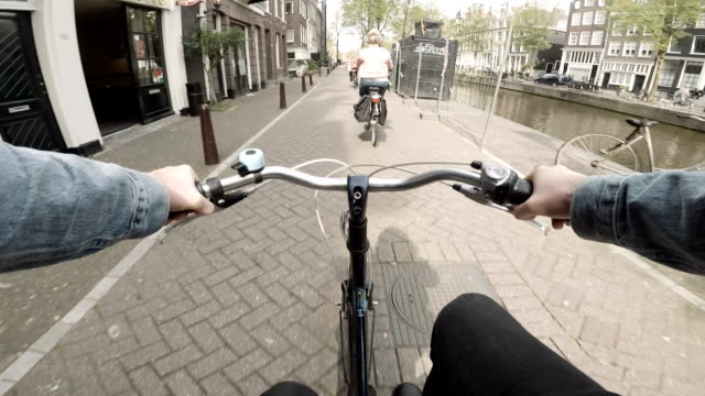 riding a bike down the streets of amsterdam, netherlands - city break stock videos and b-roll footage