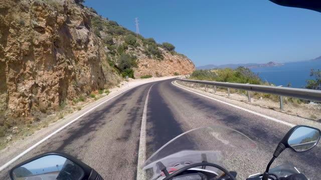 vídeos de stock, filmes e b-roll de pilotando uma moto ao longo da praia perto de antalya, ponto de vista do capacete - estrada principal estrada