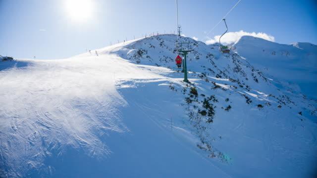stockvideo's en b-roll-footage met riding een één stoeltjeslift naar de top van besneeuwde berg in skiresort - skivakantie