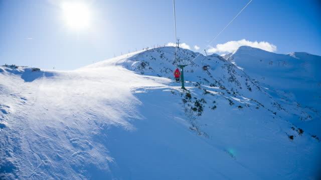 riding a single chairlift to the top of the snowcapped mountain at a ski resort - inquadratura dalla sciovia video stock e b–roll