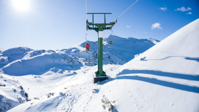 riding a ski lift at a mountain resort on a sunny winter day - seggiovia video stock e b–roll