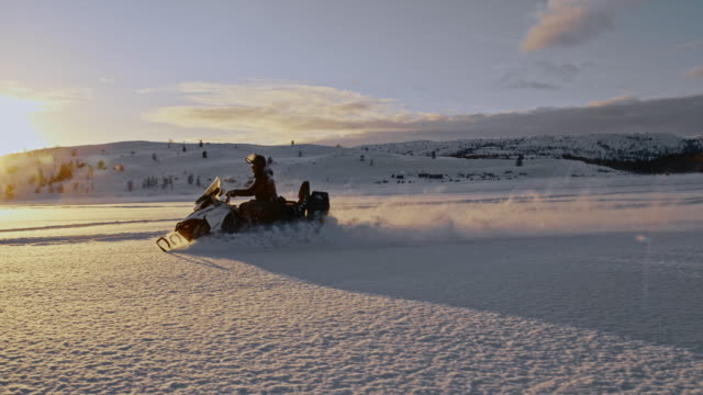 SLO MO Riding a snowmobile at sunset
