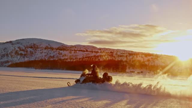vidéos et rushes de slo mo riding une motoneige à travers la neige au coucher du soleil - lieu de tournage non us