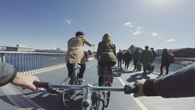 pov riding a urban road city bicycle with friends - copenhagen video stock e b–roll