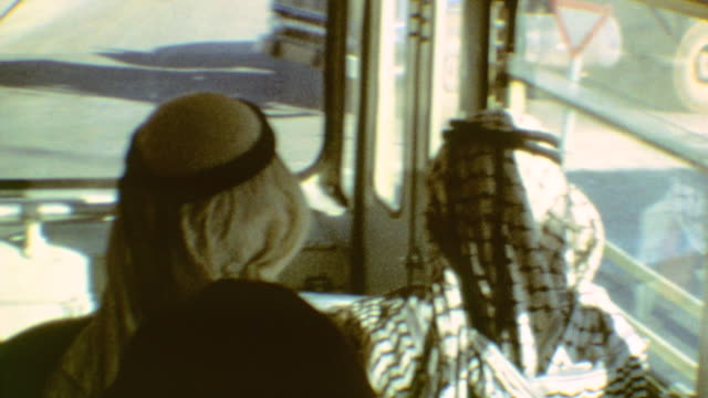 stockvideo's en b-roll-footage met riding egged bus / arab passengers in front seat / movie posters in east jerusalem / egged city bus on september 01 1974 in jerusalem israel - israëlisch palestijns conflict