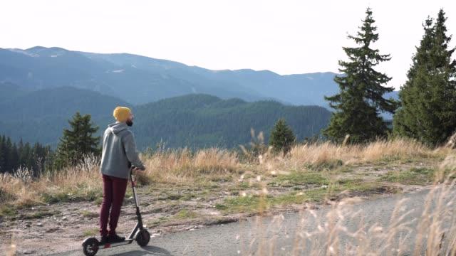 vidéos et rushes de scooter électrique d'équitation dans les montagnes - un seul jeune homme