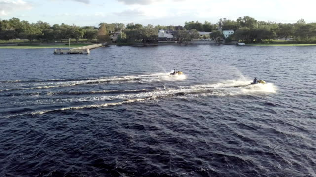 riding jet skis at golden hour - acquascooter video stock e b–roll
