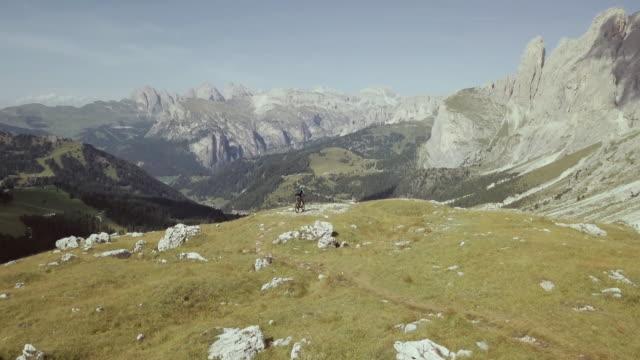 vídeos de stock, filmes e b-roll de passeios de bicicleta de montanha bicicleta em dolomitas: vista aérea de zangão - mountain bike ciclismo