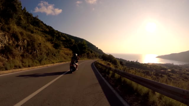 pov riding scooter on a coast road at sunset - moped stock videos and b-roll footage
