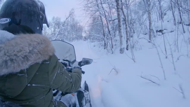 pov riding snowmobiles through snowy forest - audio available stock videos & royalty-free footage