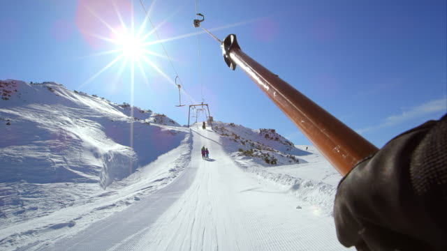 pov riding the surface ski lift up the sunny slope - winter sport stock videos and b-roll footage
