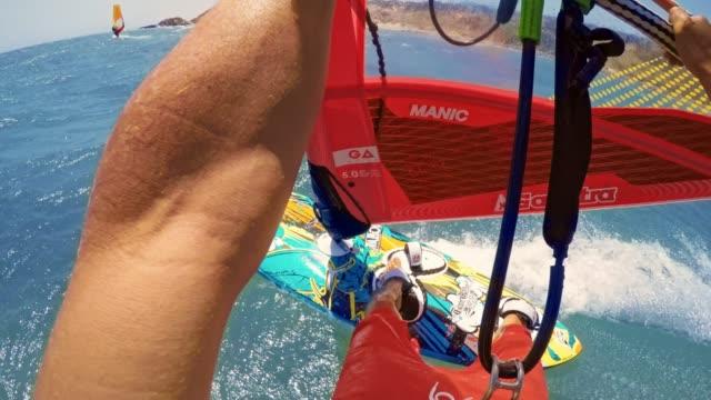 pov riding the windsurf along the coast in sunshine - aquatic sport stock videos & royalty-free footage