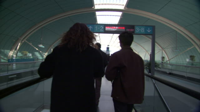 POV Riding up escalator behind other commuters to Maglev monorail boarding platform at Longyang station, Shanghai, China