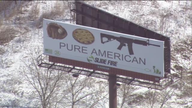 vídeos y material grabado en eventos de stock de wgn a rifle company has placed a billboard featuring a baseball mitt an apple pie and an assault rifle over the words pure american raising... - guante de béisbol