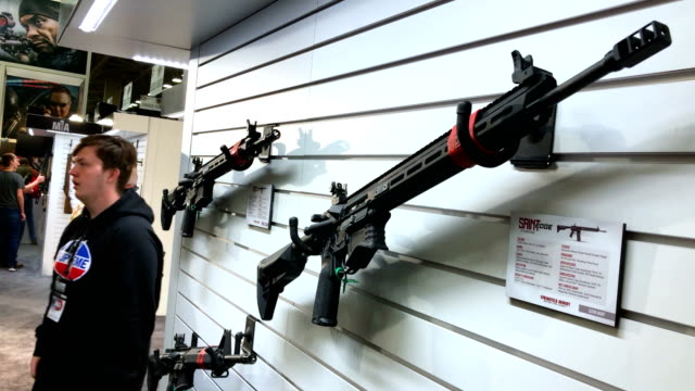 rifles are displayed during nra annual meeting exhibits at the kay bailey hutchison convention center on may 5 2018 in dallas texas the national... - gewehr stock-videos und b-roll-filmmaterial