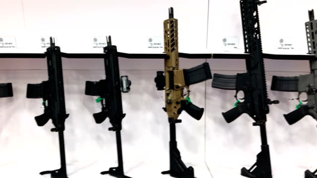 rifles are displayed during nra annual meeting exhibits at the kay bailey hutchison convention center on may 5 2018 in dallas texas the national... - national rifle association stock videos & royalty-free footage