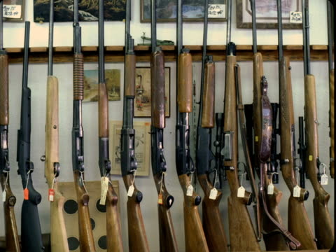 stockvideo's en b-roll-footage met ms, rifles lined up in rack in gun shop, tonopah, nevada, usa - vuurwapenwinkel