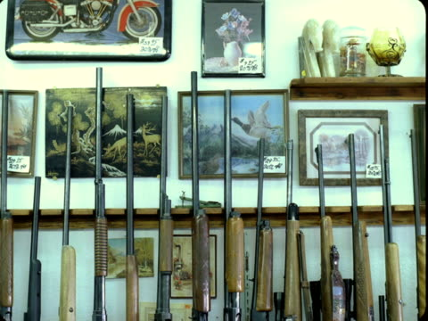 ms, rifles lined up in rack in gun shop, tonopah, nevada, usa - gun shop点の映像素材/bロール