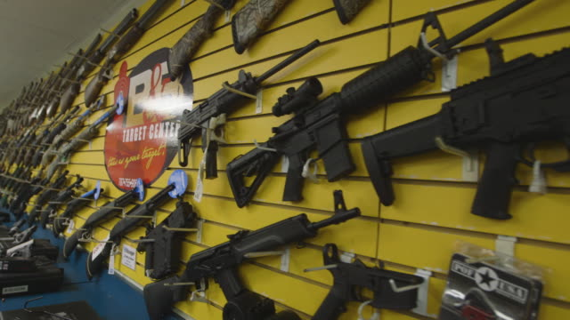 stockvideo's en b-roll-footage met rifles on the wall of a gun shop in puerto rico - vuurwapenwinkel