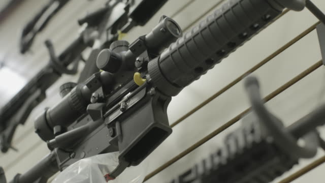 vidéos et rushes de rifles on wall of gun shop, montage close-ups - fusil
