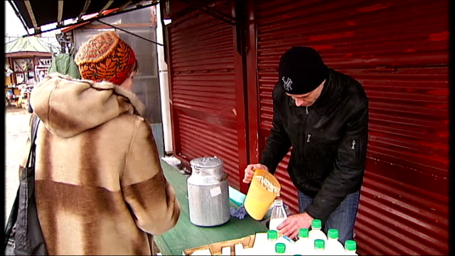 construction work / city street scenes in Winter / Frozen River Daugava Shoppers and workers at dairy produce counter milk being poured and sold...