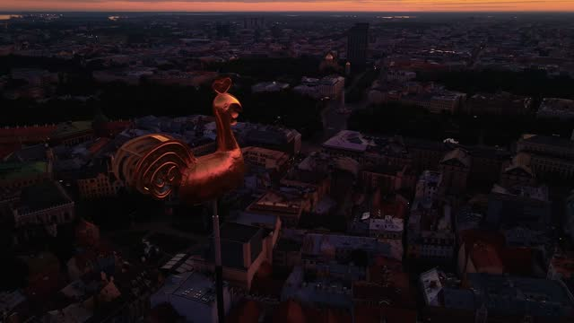 riga's golden weather cock or rooster in beautiful old town during amazing scenic sunrise aerial - state of the vatican city stock videos & royalty-free footage