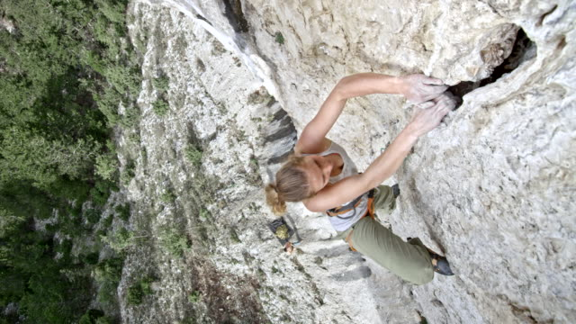 right above a female rock climber ascending a cliff - climbing stock videos & royalty-free footage