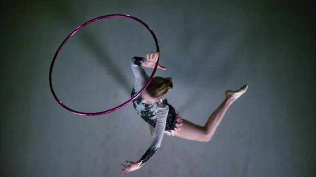 slo mo speed ramp ld right above a rhythmic gymnast rotating a hoop above her head while in an elegant pivot - dedication stock videos & royalty-free footage