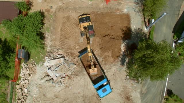 vídeos y material grabado en eventos de stock de aérea por encima de la excavadora colocar suelo en un camión en el sitio de construcción y carga en un camión - vehículo comercial terrestre