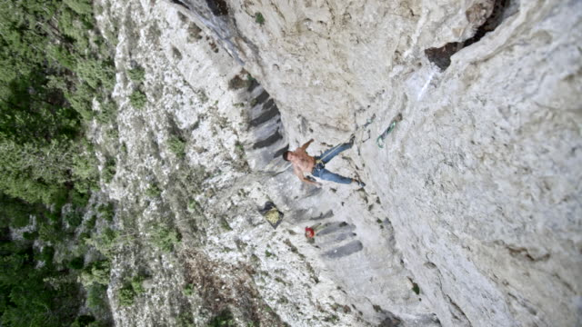 slo-mo-rechts oben die männlichen kletterer in der wand einer klippe loslassen - kletterwand kletterausrüstung stock-videos und b-roll-filmmaterial