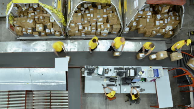time-lapse right above the warehouse workers taking packages off the conveyor belt - deposito video stock e b–roll
