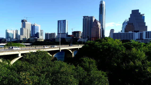 vídeos de stock e filmes b-roll de right above trees flying over town lake in austin texas skyline cityscape aerial drone view morning sunshine - town