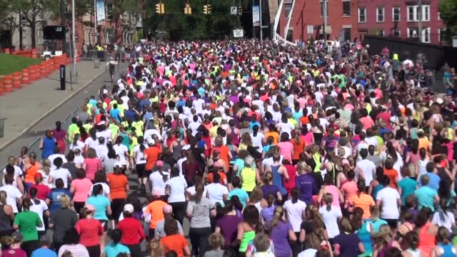 Right after start women in 5K road race head to course All Women Zoom back from top of hill Freihofers Run
