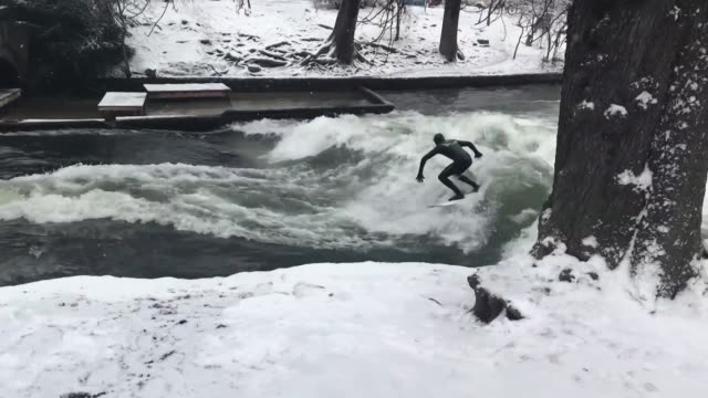 Right in the centre of Munich despite the snow and freezing temperatures brave urban adventurers surf the Eisbach man made river