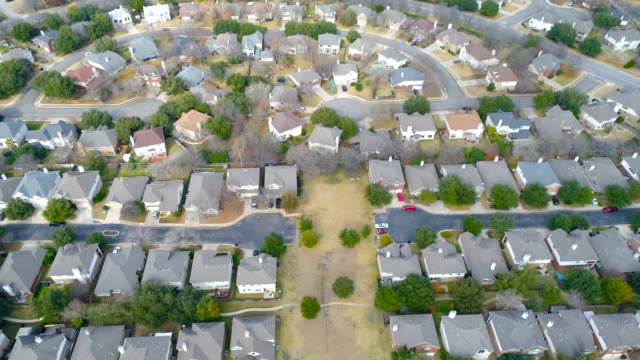 right in the middle of massive suburb neighborhood with modern layout pattern round rock , texas , aerial drone view rows and rows of houses with huge curved street around the entire community - modern rock stock videos & royalty-free footage