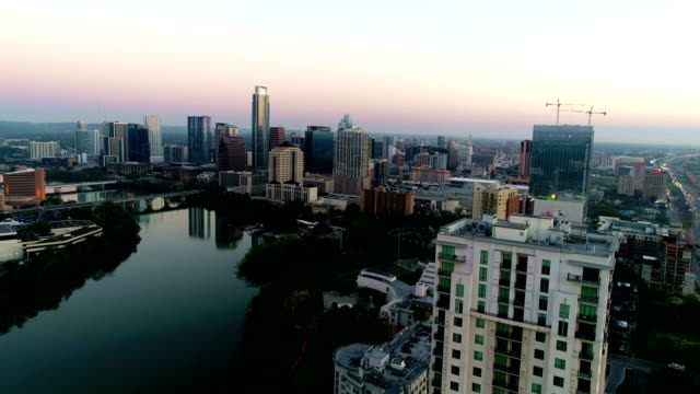right over top of condo growing austin texas capital city at sunrise - austin texas stock videos & royalty-free footage