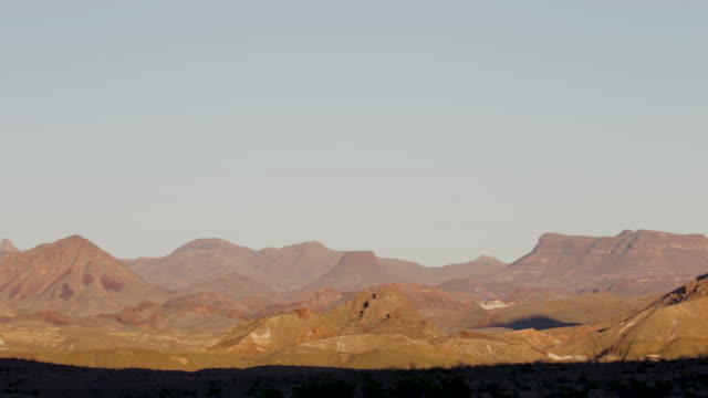 Right pan over red desert mountain landscape at sunset