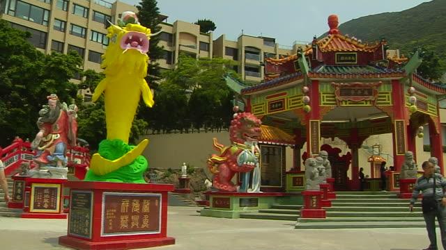 right pan shot tin hao temple entrance hong kong china - rappresentazione di animale video stock e b–roll
